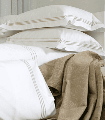 Multiple white pillows with a brown sheet