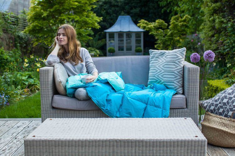 a girl sitting outside with a blanket