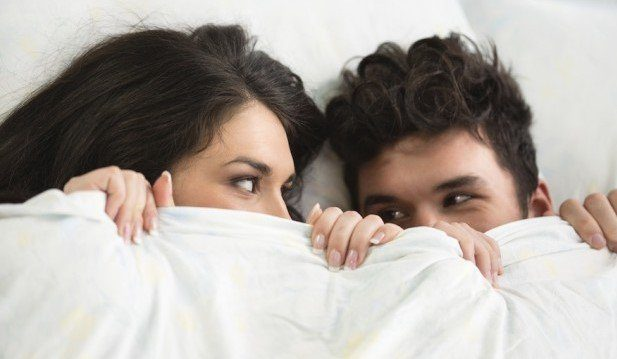 2 faces looking at one another under a blanket